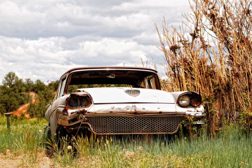 Photo of old rusty car in grassy field
